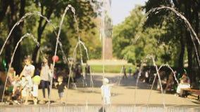 Dzieciaki bawić się z kolorowymi balonami w parku Ludzie cieszy się jaskrawego słonecznego dzień zbiory