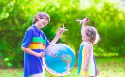 Dzieciaki bawić się z samolotami i kulą ziemską Zdjęcia Royalty Free