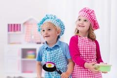 Dzieciaki bawić się z zabawkarską kuchnią obraz stock