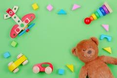 Dzieciaki bawją się tło ramę z misiem, drewnianym samolotem, samochodami i blokami na zielonym tle, obrazy royalty free