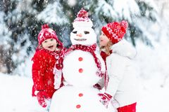 Dzieciaki buduje bałwanu Dzieci w śniegu zabawnie kierowcy sledge zimy Obraz Royalty Free