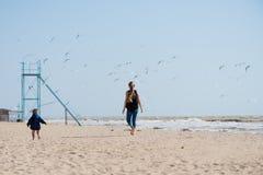 Dzieciaki chodzi na piasku wyrzucać na brzeg z seagulls fotografia royalty free