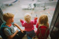 Dzieciaki czeka samolot w lotnisku, rodzinna podróż zdjęcia royalty free