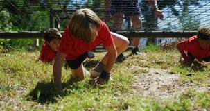 Dzieciaki czołgać się pod siecią podczas przeszkoda kursu szkolenia zbiory