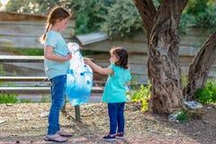 Dzieciaki czyści w forestVolunteer dzieciach z torbą na śmiecie czyści w górę ściółki, stawia plastikową butelkę w przetwarzać to zdjęcia stock