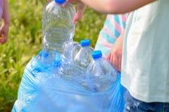 Dzieciaki czyści w parku Ochotniczy dzieci z torbą na śmiecie czyści w górę ściółki, stawia plastikową butelkę w przetwarzać torb obraz stock