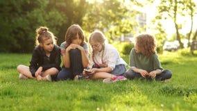 Dzieciaki i gad?ety Koledzy z klasy przechodzą each inny smartphone podczas gdy siedzący na trawie w parku projektuje ?miesznego  zdjęcie wideo