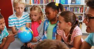 Dzieciaki i nauczyciel patrzeje kulę ziemską w bibliotece zbiory