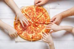 Dzieciaki i ojcowie trzyma plasterek pizza fotografia royalty free