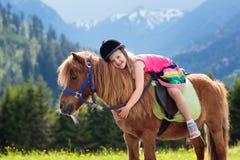 Dzieciaki jedzie konika Dziecko na koniu w Alps górach fotografia royalty free