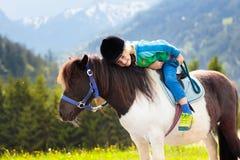 Dzieciaki jedzie konika Dziecko na koniu w Alps górach obrazy stock