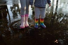 Dzieciaki jest ubranym wellingtons w kałuży Obrazy Royalty Free