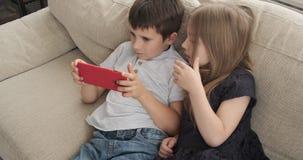 Dzieciaki kłama na kanapie z telefonem komórkowym zbiory