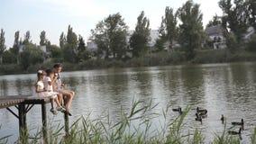 Dzieciaki karmi kaczki na molu zbiory