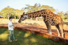 Dzieciaki karmi żyrafy w Afryka Obraz Stock