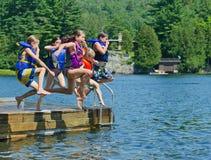 Dzieciaki ma lato zabawę skacze z doku w jezioro Obraz Royalty Free