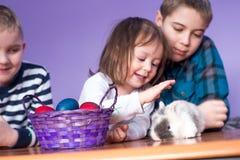 Dzieciaki mają zabawę z królikiem na wielkanocy fotografia stock