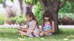 Dzieciaki malują obsiadanie na trawie pod drzewem dwa małych dziewczynek remis z kredkami w podwórzu zdjęcie wideo
