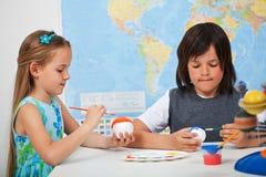 Dzieciaki maluje planety dla układu słonecznego szalkowego modela - Obrazy Royalty Free