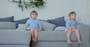 Dzieciaki oglądają tv Mali dzieci siedzi na leżanki dopatrywania kreskówkach zbiory wideo