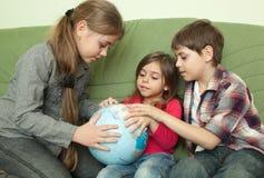 Dzieciaki patrzeje kulę ziemską Obrazy Stock