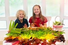 Dzieciaki podnoszą kolorowych jesień liście dla szkolnej sztuki zdjęcie royalty free
