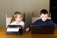 Dzieciaki pracuje na starym maszyna do pisania i laptopie zdjęcia stock
