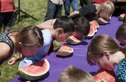 Dzieciaki przy arbuza łasowania konkursem. Obraz Stock
