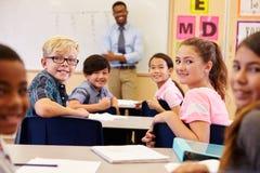 Dzieciaki przy ich biurkami w sala lekcyjnej kręceniu stawiać czoło kamerę obraz stock