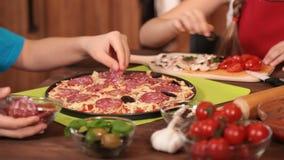 Dzieciaki robi pizzy kładzeniu na różnorodnej polewie w domu zbiory