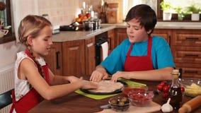 Dzieciaki robi pizzy w domu - rozciągać ciasto zbiory