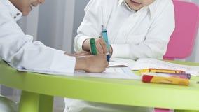 Dzieciaki rysuje z barwionymi kredkami przy stołem obraz stock