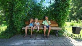 Dzieciaki siedzi na ławce i je lodów rożki zbiory