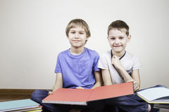 Dzieciaki siedzi na czytelniczych książkach i podłoga w domu obrazy royalty free