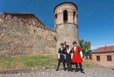 Dzieciaki stoi past cegły wierza dziejowy miasto Telavi w tradycyjnych Gruzińskich kostiumach Zdjęcie Stock