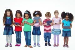 Dzieciaki stoi wpólnie trzymać pastylki i telefony Fotografia Royalty Free