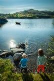 Dzieciaki thowing skały w wodzie w Lofoten, Norwegia Obraz Royalty Free