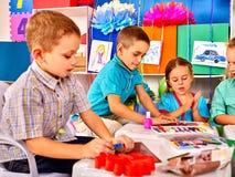 Dzieciaki trzyma barwiącego papier na stole wewnątrz Zdjęcie Royalty Free