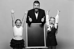 Dzieciaki trzyma ręki up stoją obok blackboard i nauczyciela, kopii przestrzeń Dziewczyny i mężczyzna z szczęśliwymi twarzami Ucz obraz stock