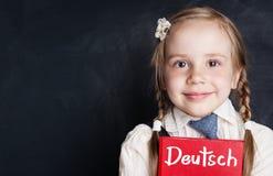 Dzieciaki uczą się niemiec Ciekawa dziecko dziewczyna z niemiec książką zdjęcie royalty free