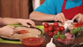 Dzieciaki wręczają rozprzestrzeniać kumberland na pizzy cieście zdjęcie wideo