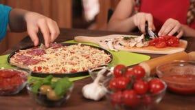Dzieciaki wręczają stawiać salami plasterki na pizzy zbiory
