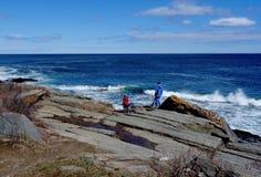 Dzieciaki wspina się skały na wybrzeżu Maine w Kwietniu fotografia stock