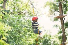 Dzieciaki wspina się w przygoda parku Chłopiec cieszy się pięcie w arkanie Obraz Stock
