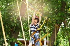Dzieciaki wspina się w przygoda parku Chłopiec cieszy się pięcie w arkanie Fotografia Royalty Free