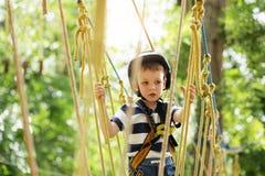 Dzieciaki wspina się w przygoda parku Chłopiec cieszy się pięcie w arkanie Zdjęcia Stock
