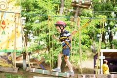 Dzieciaki wspina się w przygoda parku Chłopiec cieszy się pięcie w arkanie Zdjęcie Stock