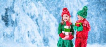Dzieciaki z Bożenarodzeniowymi teraźniejszość w śnieżnym zima parku zdjęcia royalty free