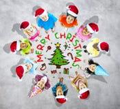Dzieciaki z bożymi narodzeniami z drzewem w Popielatym tle Zdjęcie Stock