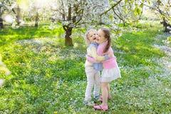 Dzieciaki z czereśniowego okwitnięcia kwiatem chłopcy tła Wielkanoc jajka miłych jaj trawy zielone świeżego ukryte hunt wyizolowa Obrazy Royalty Free